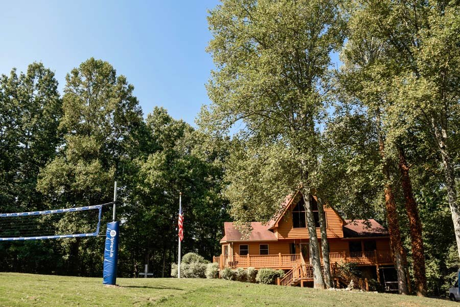 View of the cabin and volleyball net at a non profit rehab center in Tennessee