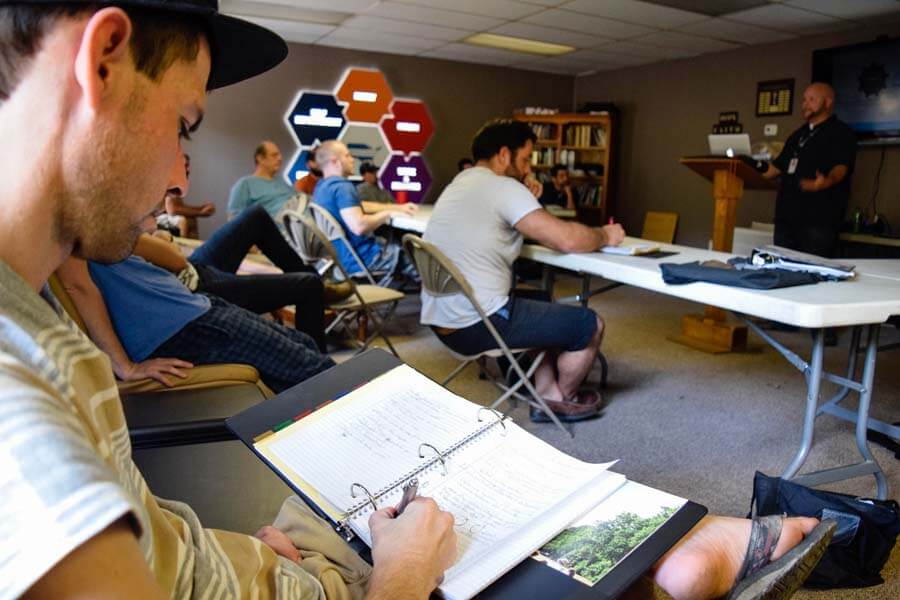 Group of men taking notes as part of their Christian addiction recovery curriculum